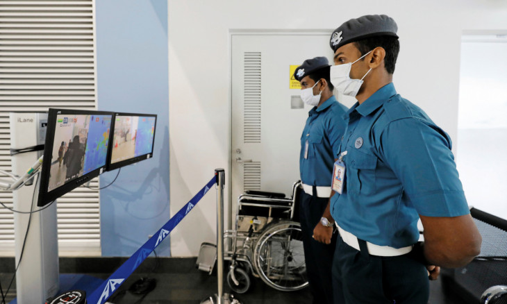 Bandaranaike international airport security officials wears masks as they inspect passengers using a scanner monitoring their temperature following the new coronavirus outbreak from China, at Bandaranaike international airport in Katunayake