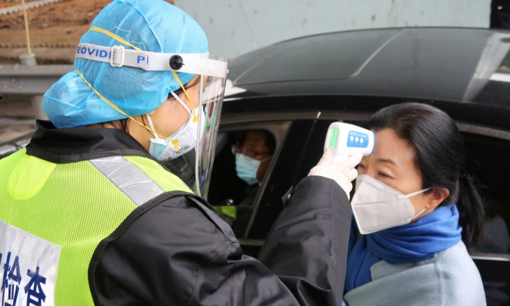 A security officer in a protective mask checks the temperature of a passenger following the outbreak of a new coronavirus, at an expressway toll station on the eve of the Chinese Lunar New Year celebrations, in Xianning