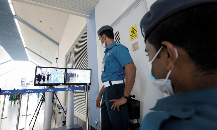 Bandaranaike international airport security officials wears masks as they inspect passengers using a scanner monitoring their temperature following the new coronavirus outbreak in China, at Bandaranaike international airport in Katunayake