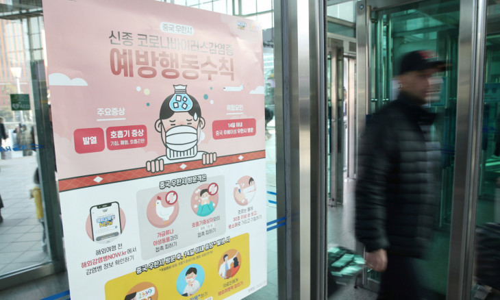 A man walks past a notice for passengers about new coronavirus that has broken out in China, at Seoul railway station in Seoul