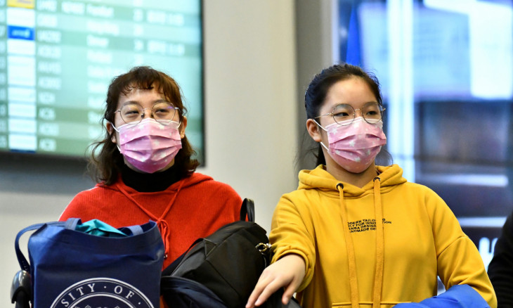 Travellers wearing masks arrive on a direct flight from China at Vancouver International Airport