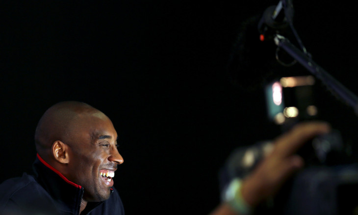 FILE PHOTO: U.S. basketball player Kobe Bryant smiles as he answers a reporter's question during a news conference in the Olympic media centre in London