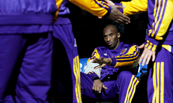 FILE PHOTO: Los Angeles Lakers Kobe Bryant reaches his hand out to teammates as the Lakers are announced before the start of the first half of their NBA basketball game against the Boston Celtics at TD Garden in Boston