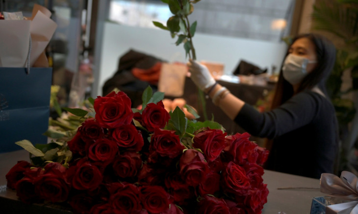 Florist Zhen Zhen prepares a flower bouquet to deliver on Valentine's Day at the Mulan Blossom floweshop in Beijing