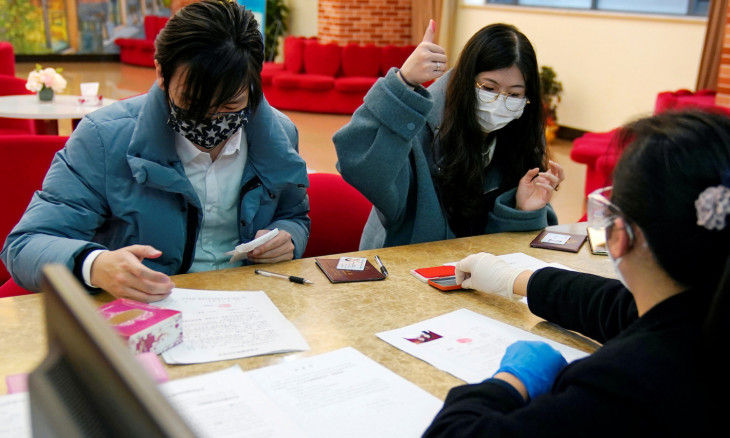 Wang, 32, and his wife Shi, 30, wearing masks are seen at a registration session at a marriage registry office on Valentine's Day in Shanghai