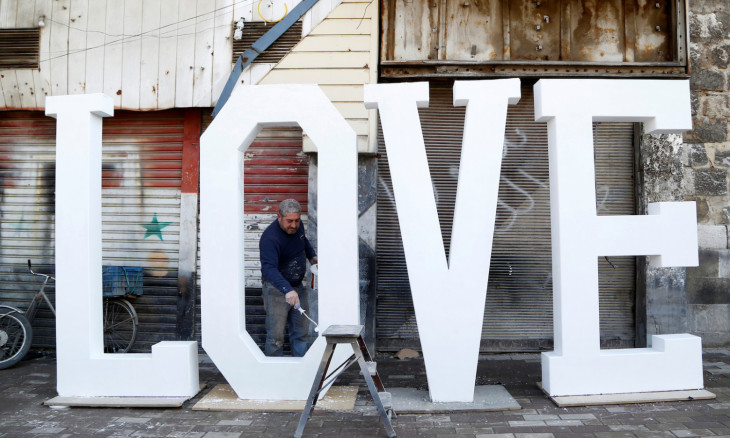 """A man paints letters that create the word """"Love"""" for Valentine's Day in Damascus"""
