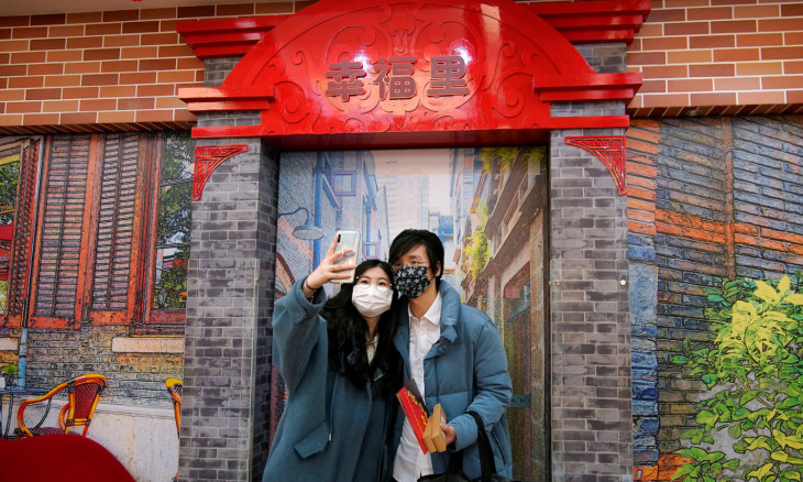 Wang, 32, and his wife Shi, 30, pose for a selfie as Wang holds their marriage certificates at a marriage registry office on Valentine's Day in Shanghai