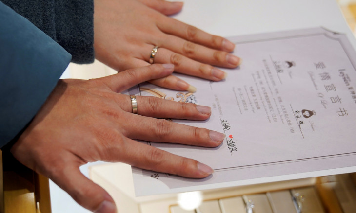 Wang, 32, and his wife Shi, 30, show their wedding rings at a shopping mall on Valentine's Day in Shanghai