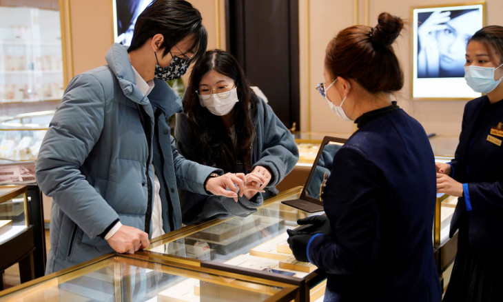 Wang, 32, and his wife Shi, 30, wearing masks buy wedding rings at a shopping mall on Valentine's Day in Shanghai