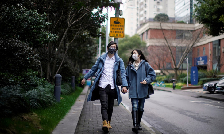 Wang, 32, and his wife Shi, 30, wearing masks walk on a street on Valentine's Day in Shanghai