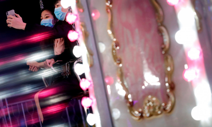 A couple wears masks to protect against an outbreak of a coronavirus as they ride on a carnival on Valentine's Day in Hong Kong