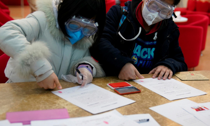 Jia, 29, and his wife Su, 28, wearing masks take impression of fingerprints at a registration session at a marriage registry office on Valentine's Day in Shanghai