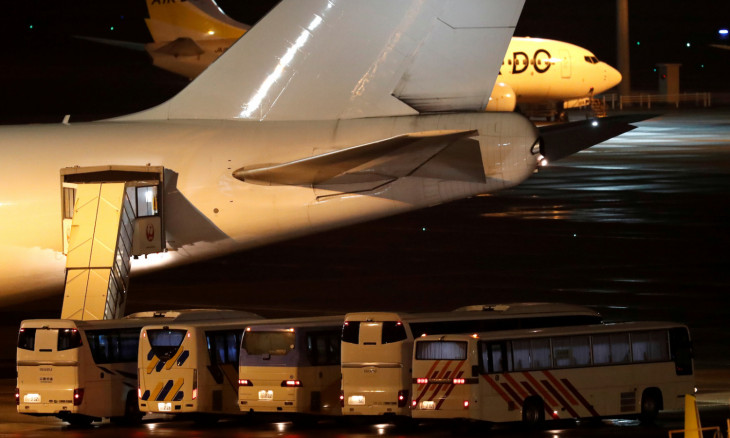 Buses believed to carry the U.S. passengers of the cruise ship Diamond Princess, where dozens of passengers were tested positive for coronavirus, are parked next to an airplane at Haneda airport in Tokyo