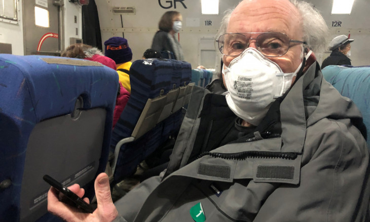 Phil Courter, a U.S. passenger on board the Diamond Princess cruise ship, wears a face mask on a chartered evacuation aircraft to fly back to the United States, at Haneda airport in Japan