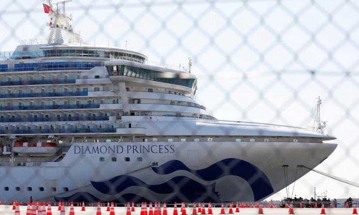 FILE PHOTO: The Diamond Princess, where many passengers have tested positive for coronavirus, is seen through steel fence at Daikoku Pier Cruise Terminal in Yokohama