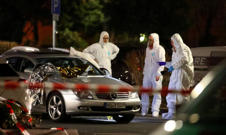 Forensic experts work around a damaged car after a shooting in Hanau near Frankfurt