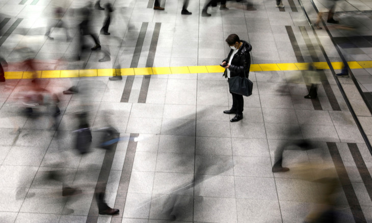A man wearing a protective face mask stands at the Shinagawa station in Tokyo