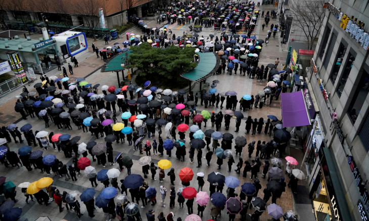 People wearing masks after the coronavirus outbreak wait in a line to buy masks as it rains in front of a department store in Seoul