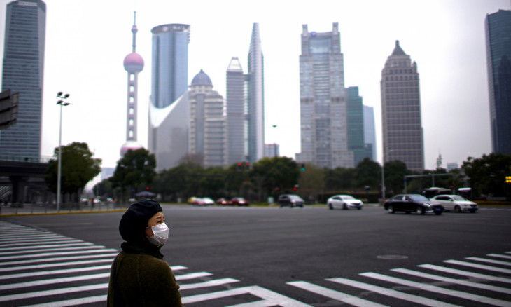 A woman wearing a protective mask is seen in Shanghai, China, as the country is hit by a novel coronavirus outbreak, at the Pudong financial district in Shanghai