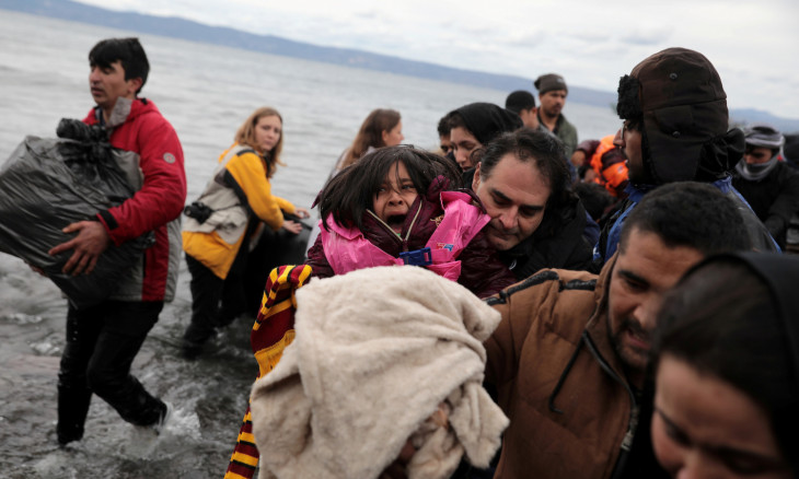 A girl reacts as migrants from Afghanistan arrive on a dinghy on a beach near the village of Skala Sikamias on the island of Lesbos