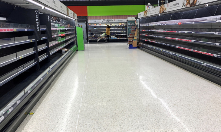 A shopper is seen at the end of an empty aisle in an Asda supermarket in Manchester