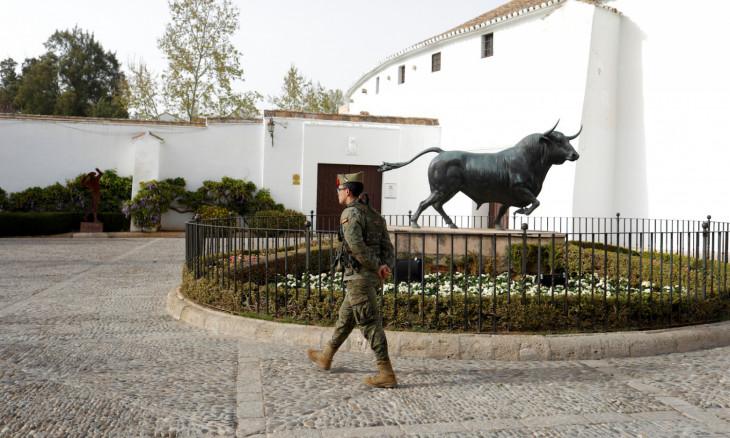 A Spanish legionnaire patrols in an empty street in downtown Ronda