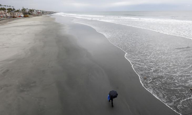 A man walks along an empty beach during the global outbreak of the coronavirus disease (COVID-19) in Oceanside, California,