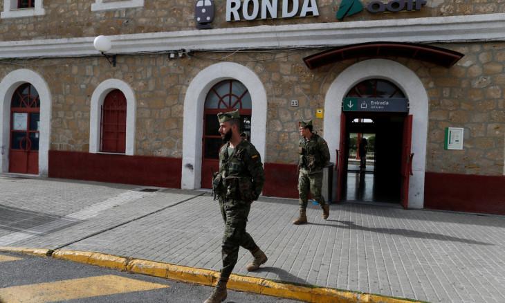 Spanish legionnaires patrol an empty train station in downtown Ronda