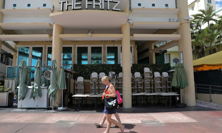 Tourist walk in an empty area of South Beach after local authorities closed bars, restaurants and some areas of beaches to the public for precaution due to coronavirus disease (COVID-19) spread, in Miami Beach