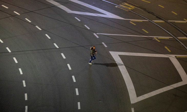 A woman runs alongs an empty street just before a curfew imposed to prevent the spread of coronavirus disease (COVID-19) in Belgrade