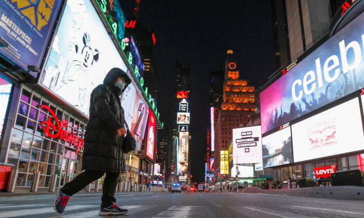 A person in a face mask walks through an almost empty Times Square as the coronavirus disease (COVID-19) outbreak continued in Manhattan, New York City