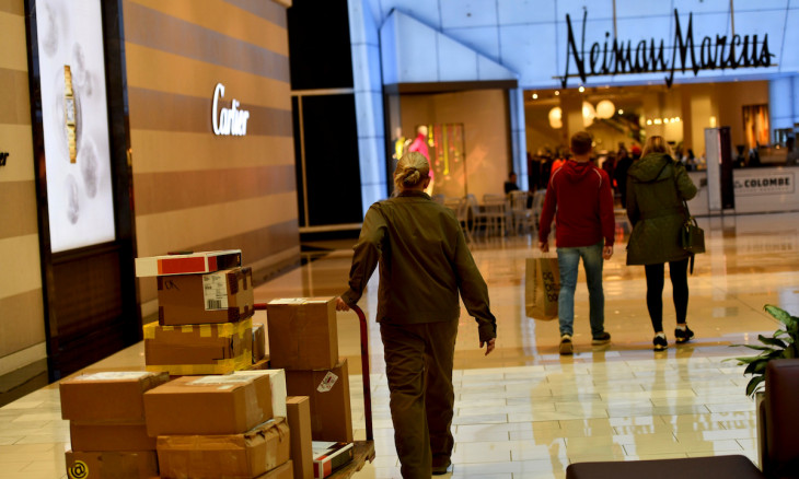 FILE PHOTO: A delivery of boxes is wheeled as shoppers walk towards a Neiman Marcus as holiday shopping accelerates at the King of Prussia Mall