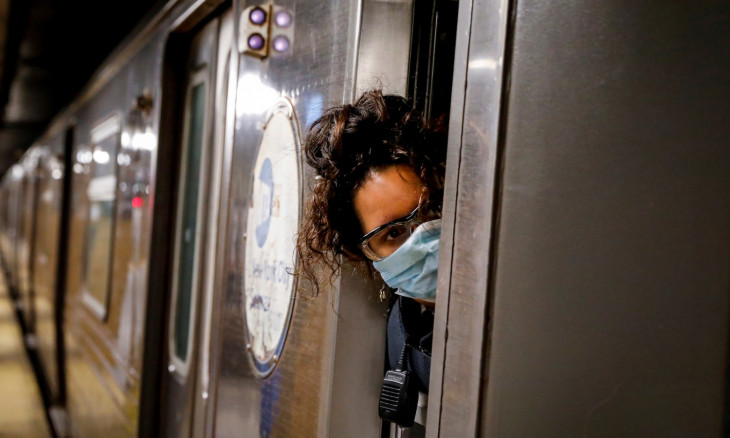 A conductor looks out of an MTA subway car at a stop, during the outbreak of the coronavirus disease (COVID-19) in Brooklyn, New York