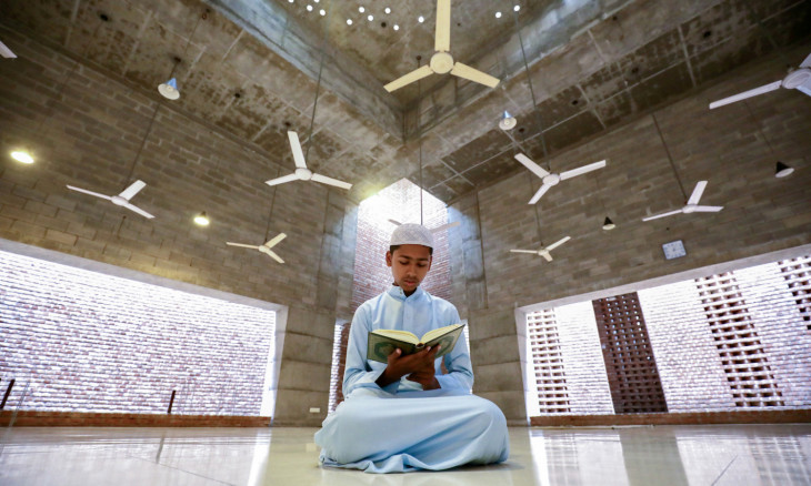 A muslim boy recites Koran at the Bait Ur Rouf Mosque during Ramadan amid concerns over the coronavirus disease(COVID-19) outbreak in Dhaka