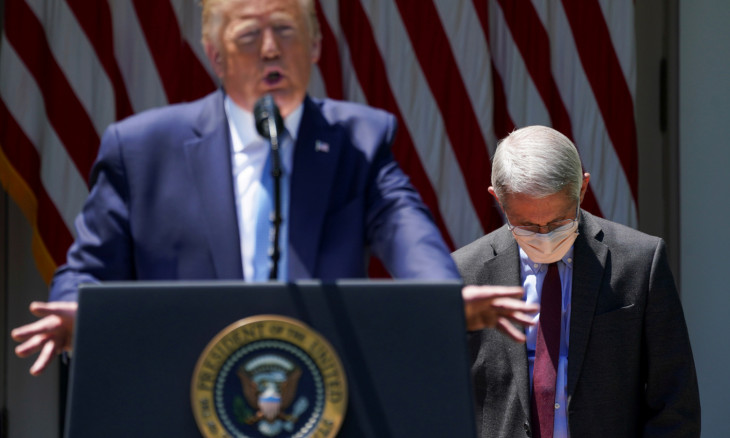 Fauci looks down as Trump speaks about efforts to develop a coronavirus vaccine at the White House in Washington