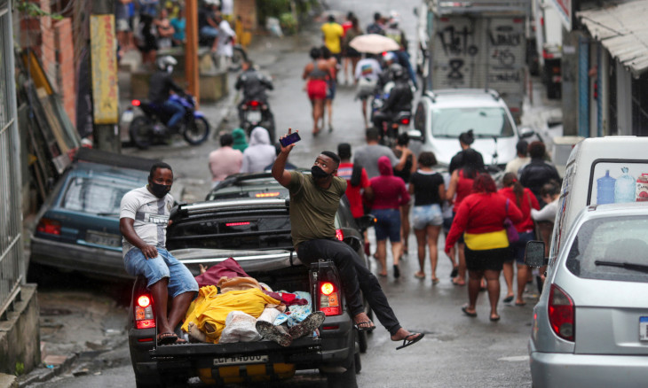 Residents wearing protective masks transport dead bodies after a police operation against drug gangs in Rio de Janeiro