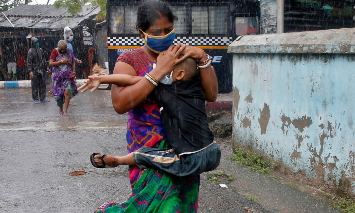 A woman carries her son to a safer place before Cyclone Amphan makes its landfall, in Kolkata