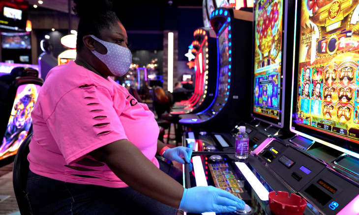 A woman wearing a mask and gloves plays a slot machine at the recently reopened Lucky Star Casino in El Reno