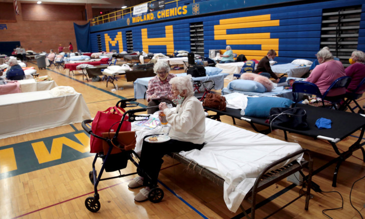 Dot Costello, 101 years old, sits on a bed at an evacuee centre after being evacuated from her home along the Tittabawassee River, after several dams breached, in Midland