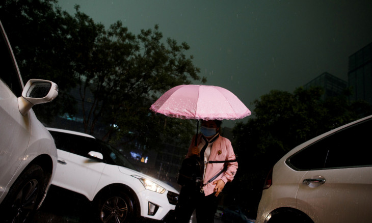 A woman wearing a protective mask carries an umbrella as a sudden thunderstorm darkens the mid-afternoon sky in Beijing