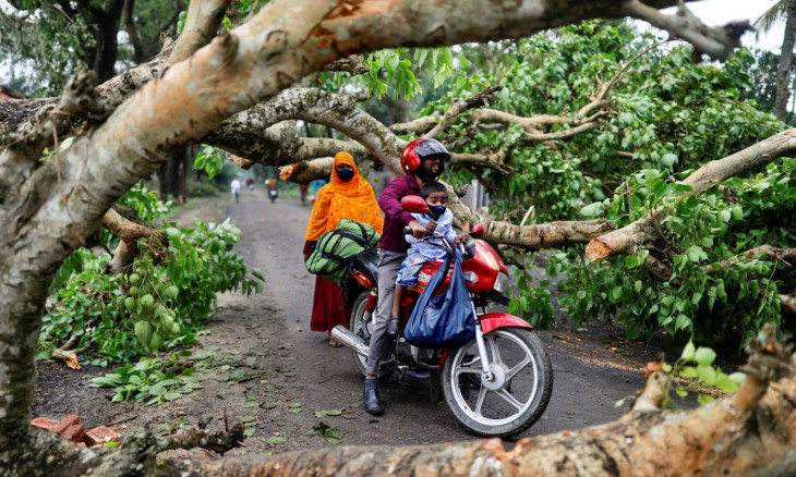 A man with a child ride on motorbike in the street blocked by trees that were uprooted by the cyclone Amphan, in Satkhira