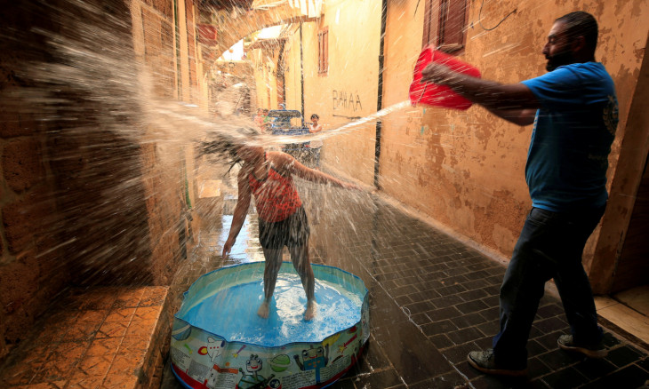 A man throws water on a girl playing in a pool in Sidon
