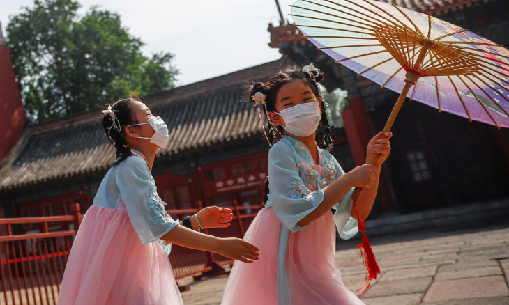Children wearing protective face masks play near the entrance to the Forbidden City on the day of the opening of the National People's Congress (NPC) following the outbreak of the coronavirus disease (COVID-19), in Beijing