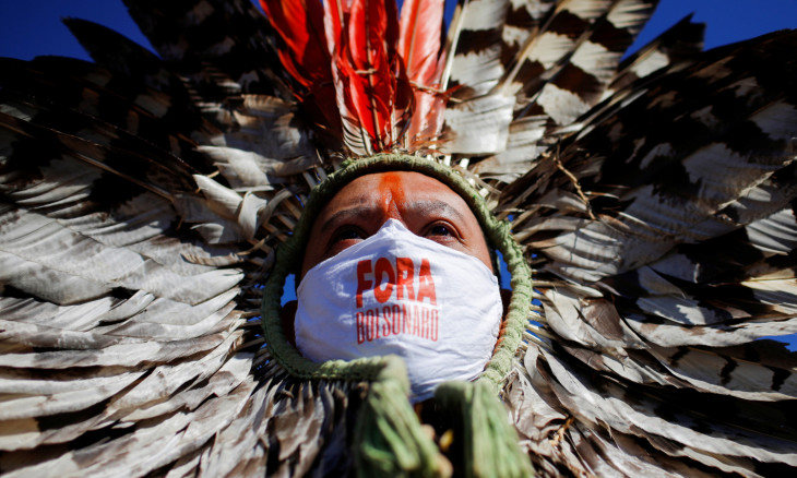 """ndigenous Leader Kretan Kaingang of the Kaingang tribe, wearing a protective face mask reading """"Out Bolsonaro"""""""