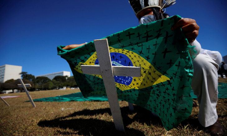 An activist puts a Brazilian flag painted with crosses on a cross