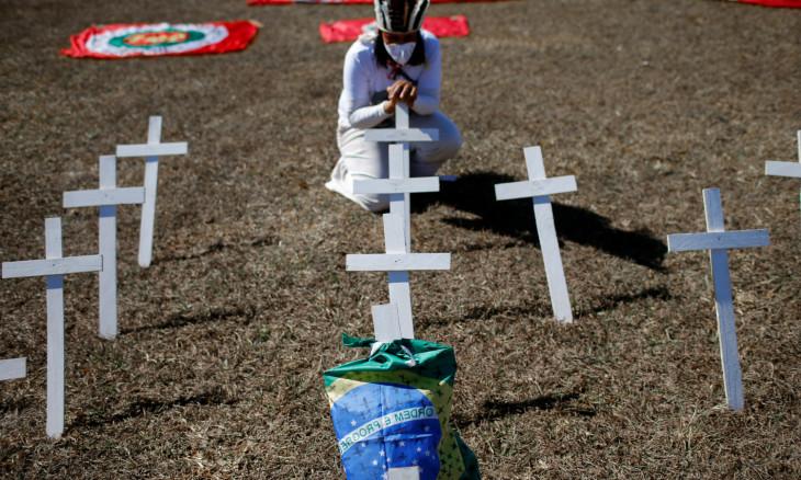 An activist kneels next to crosses