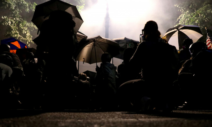 Demonstrators shelter from tear gas behind umbrellas