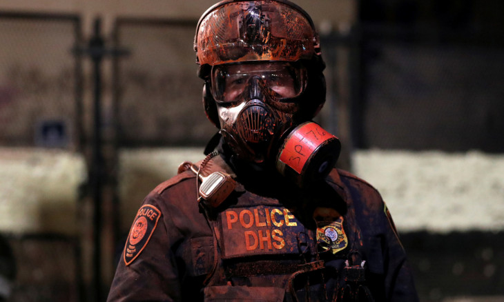 A federal law enforcement officer is covered in red paint