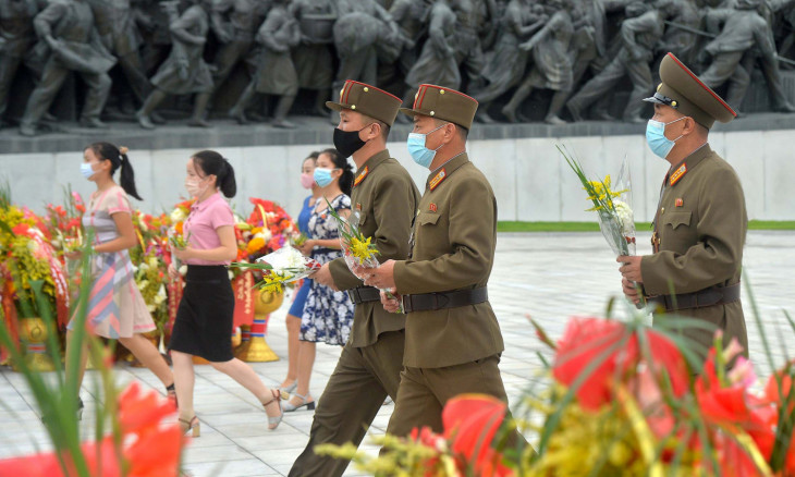 People pay floral tributes to statues of North Korea's founder
