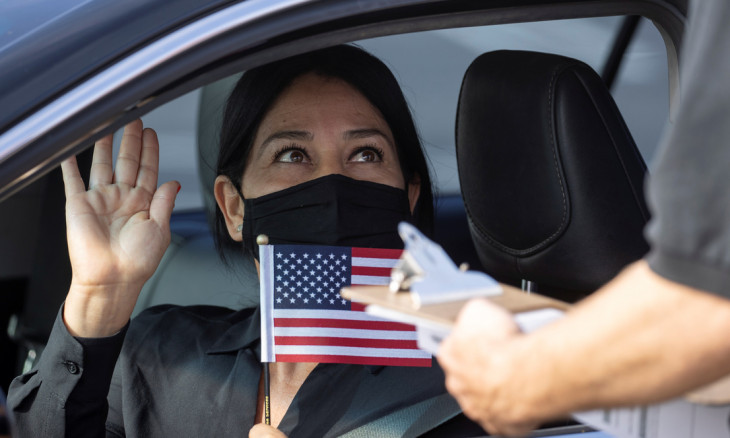 A women holds a flag as a U.S. immigration officer administer the oath during a swearing-in of newly naturalized United States citizens